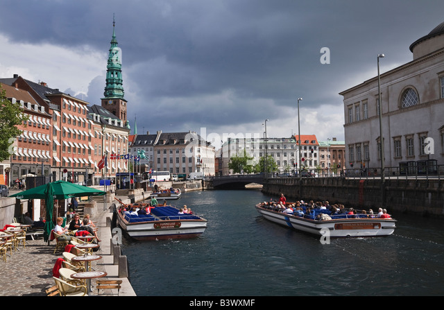 Canal tour boats and view towards Nikolaj Kirke from Gammel Strand, Copenhagen, Denmark - Stock Image