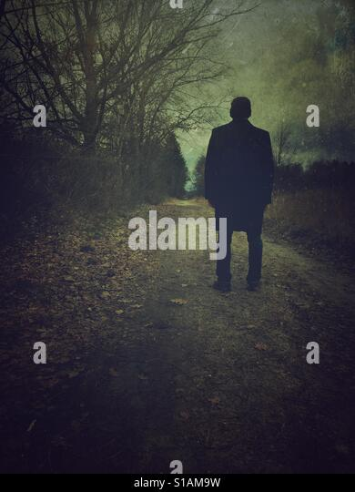 Rear view of a man wearing a coat standing on a countryside road - Stock-Bilder