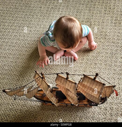 Baby reaching for a model ship sitting on the floor - Stock Image