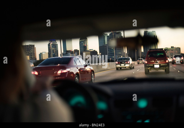 Driving in traffic on freeway, city skyline in background - Stock Image