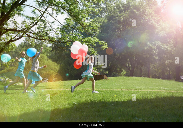 Girls running in park with balloons, Munich, Bavaria, Germany - Stock Image