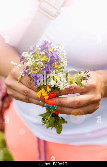 Young woman holding bunch of wild flowers - Stock Image