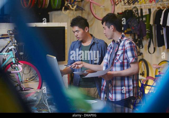 Two young men in bike shop using computer - Stock Image