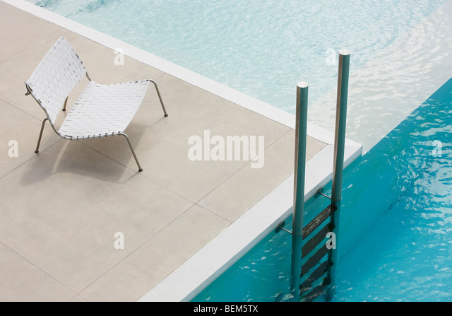 Chair at edge of pool near ladder - Stock Image