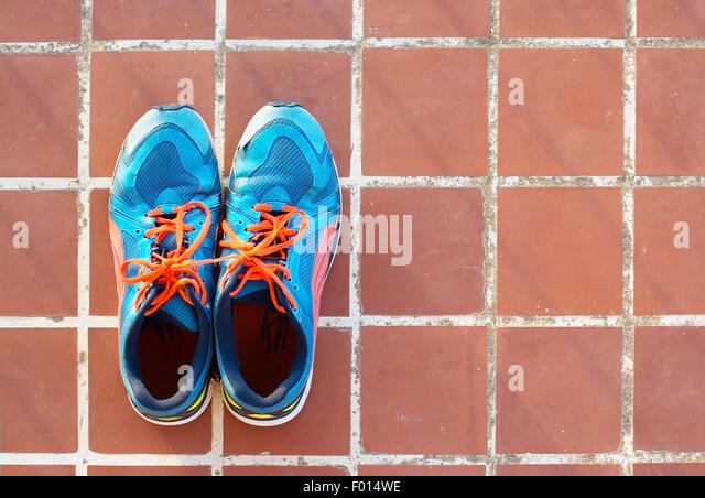 Blue sports shoes on terracotta floor square tile background texture. - Stock-Bilder