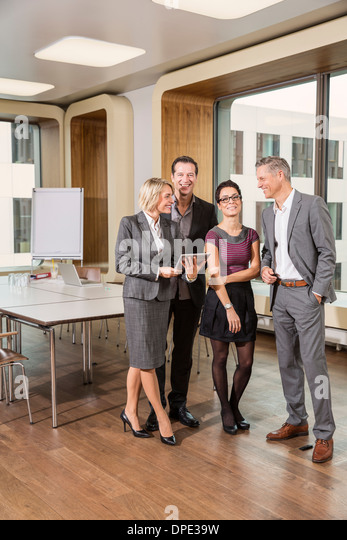 Businesspeople standing in conference room - Stock-Bilder