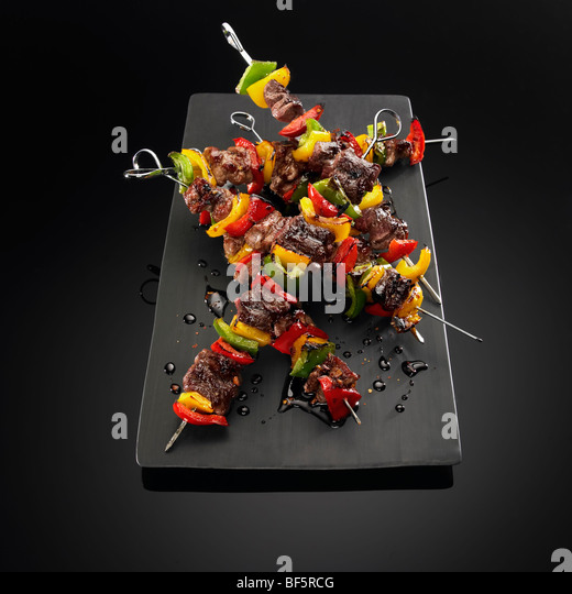 Beef and vegetable kebabs on skewers, on a black background. - Stock Image