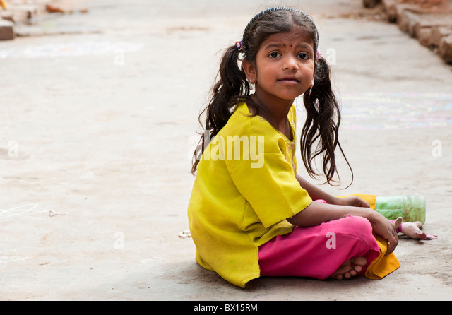 Smiling happy Indian village girl with a soft toy sitting in the street - Stock Image