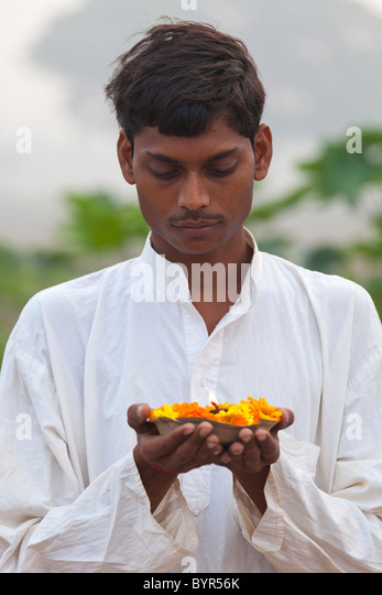 india, Uttar Pradesh, young hindu man holding prayer lamp and marigolds - Stock Image