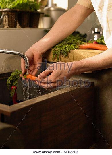 Man washing carrot - Stock Image