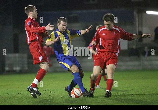 Richard Oxby of Romford is sandwiched by Andrew Howell (L) and Tony Russell of Aveley - Romford vs Aveley - Ryman - Stock Image