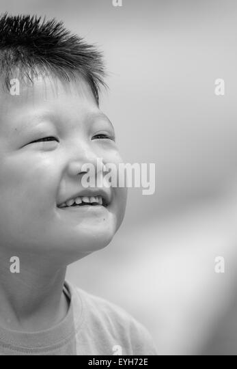 Black and white Portrait of a little mongoloid boy happy and smiling with copy space - Stock Image