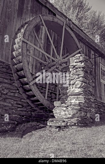 An old grist mill with water wheel in black and white. - Stock-Bilder