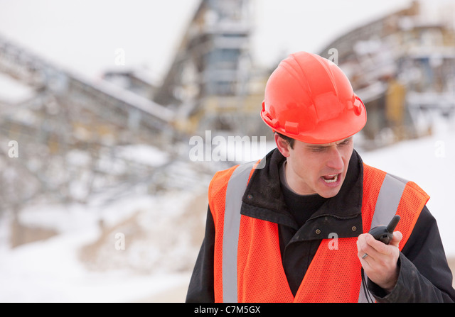 Engineer yelling on a walkie-talkie - Stock Image