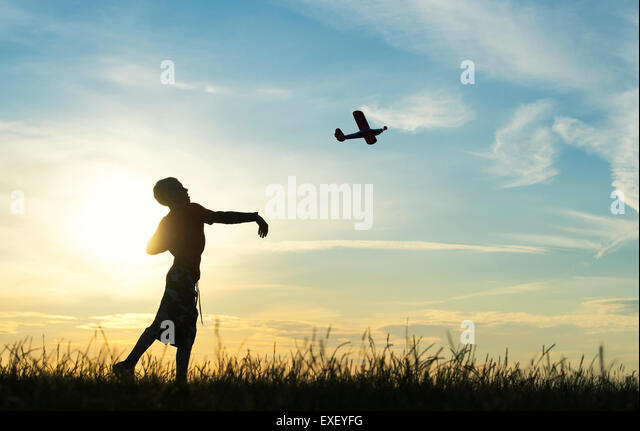 Boy throwing a model airplane at sunset. Silhouette - Stock Image