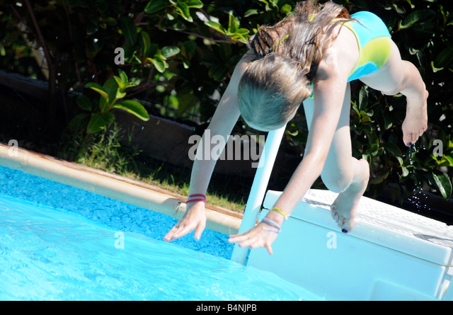 Royalty free photograph of young girl diving into a swimming pool on summer holiday. - Stock Image
