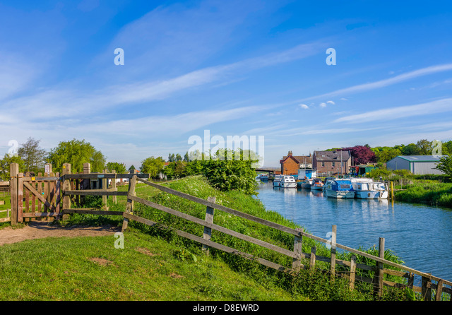River Hull with boats moored along the bank with fencing and houses on a bright sunny day with blue sky, Yorkshire, - Stock Image