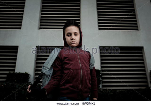 Boy carrying backpack, looking down - Stock-Bilder