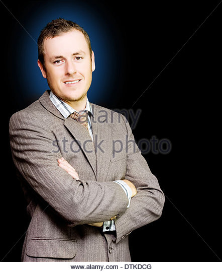 Happy ambitous young man smiling with self confidence standing with arms folded as befitting his position of authority - Stock Image