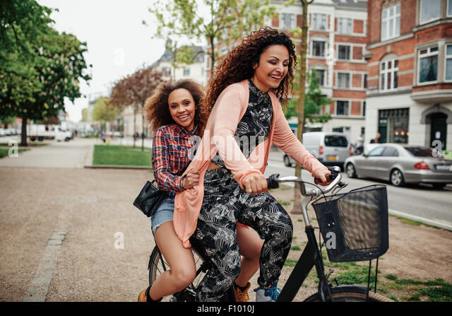 Cheerful young women enjoying bicycle ride on city street. Two young girls together riding on one bicycle. - Stock Image