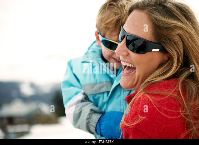 Skiing mother carrying toddler son - Stock Image
