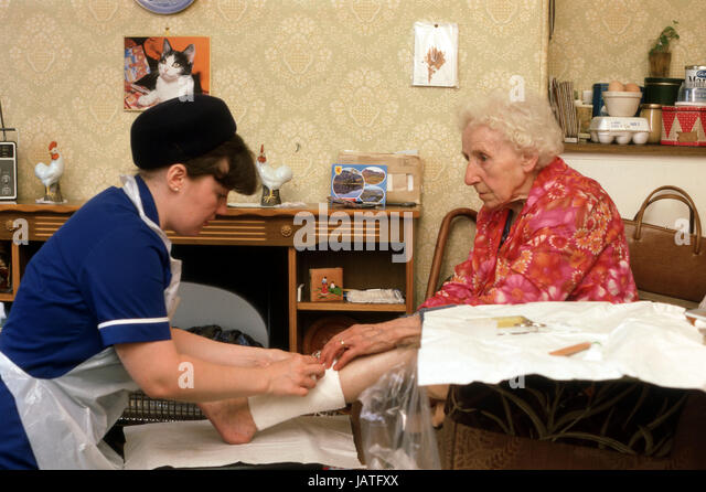 home help carers district nurse on a home visit tending to elderly woman with leg ulcers - Stock Image
