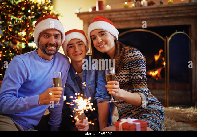 Family of three looking at camera on Christmas evening - Stock Image