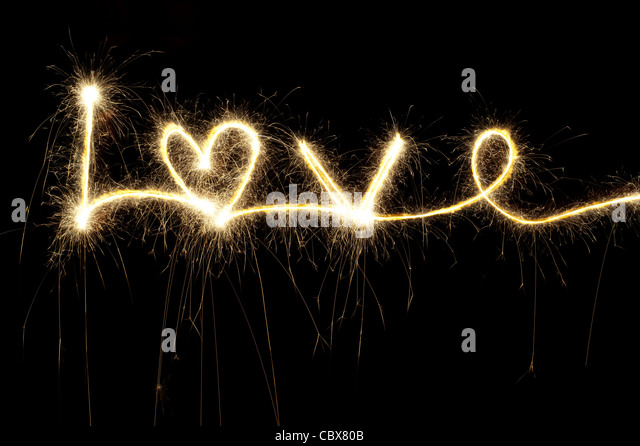 LOVE written with a sparkler at night including a heart shape - Stock-Bilder