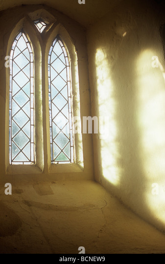 Soft light streaming through two upright frosted diamond leaded windows and projected onto cream wall of deep recess - Stock-Bilder