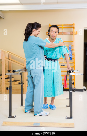 Physical Therapist Assisting Male Patient In Walking - Stock Image