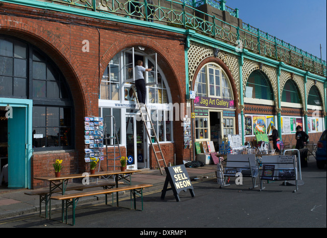 Spring clean under the arches on Madeira Drive, Brighton, England - Stock Image