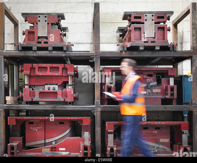 Worker with clipboard walking past press moulds in sheet metal factory - Stock-Bilder