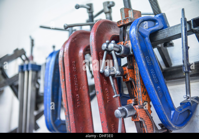 Assorted steel clamps in engineering factory - Stock Image