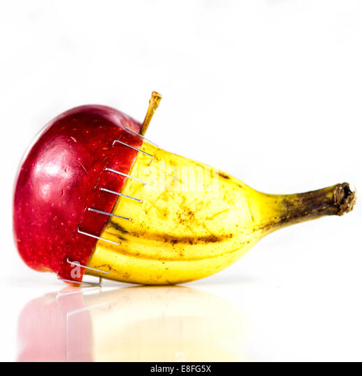 Apple and banana stapled together - Stock Image