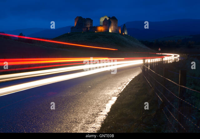 Ruthven Barracks (ruin) is a scheduled monument, near Ruthven in Scotland, lit at night with car light trails on - Stock Image