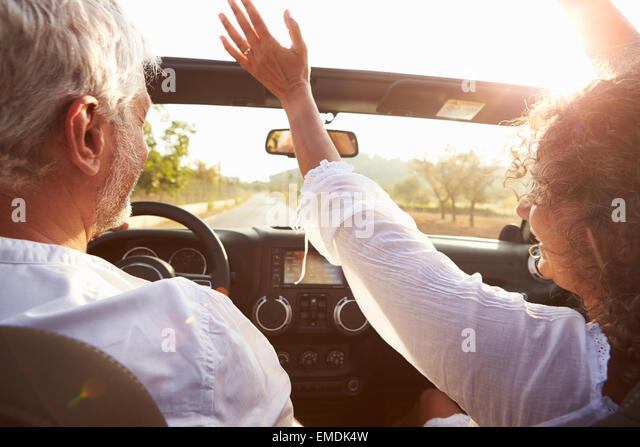 Mature Couple Driving Along Country Road In Open Top Car - Stock Image