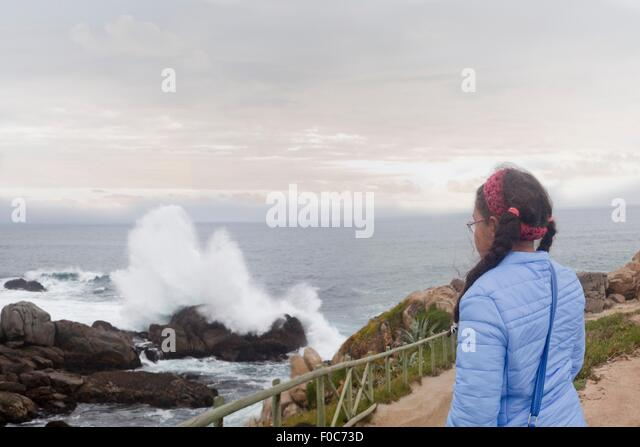 Young girl watching waves crash on rocks, Valparaiso, Chile - Stock Image
