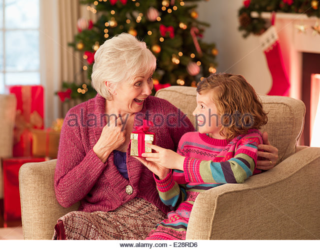 Girl and grandmother holding Christmas gift - Stock Image