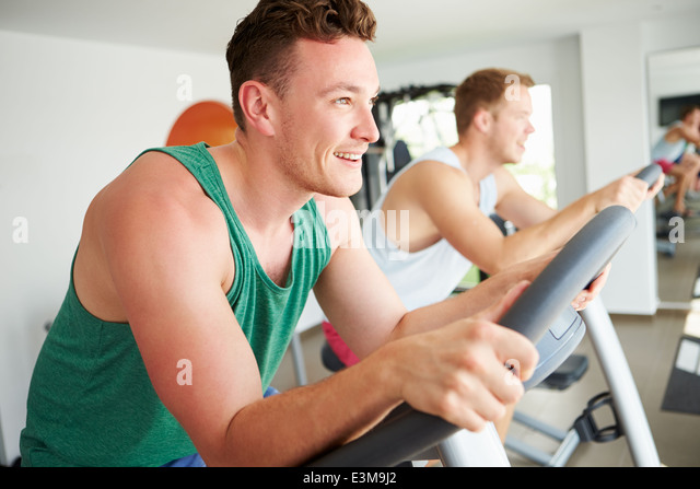 Two Young Men Training In Gym On Cycling Machines Together - Stock-Bilder