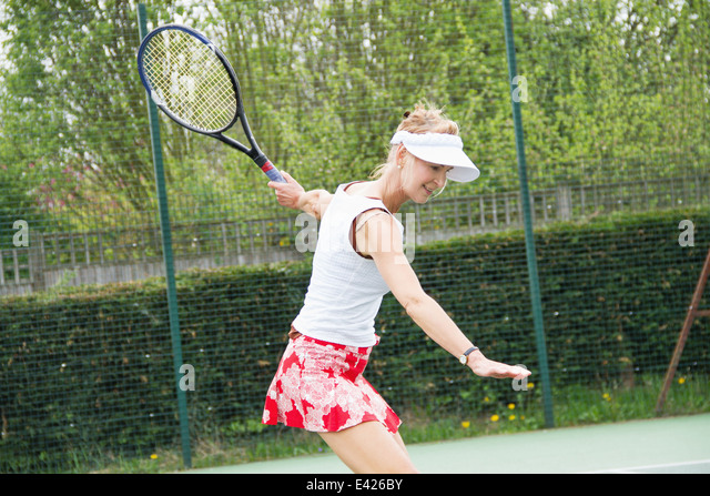 Mature woman playing tennis - Stock Image