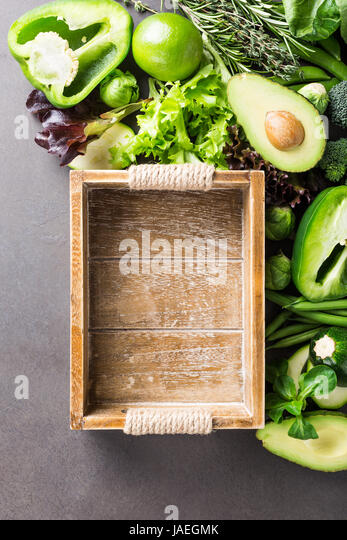 Background with assorted green vegetables, salad, avocado, bell pepper and Brussels sprouts with wooden tray on - Stock Image