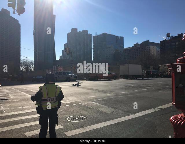 Crossing guard monitoring traffic near a Manhattan crosswalk. - Stock Image