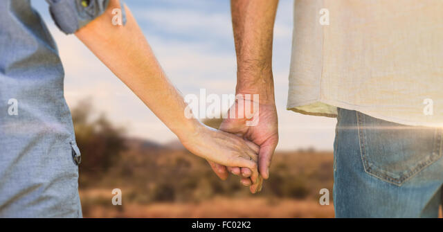 Composite image of couple holding hands in park - Stock-Bilder