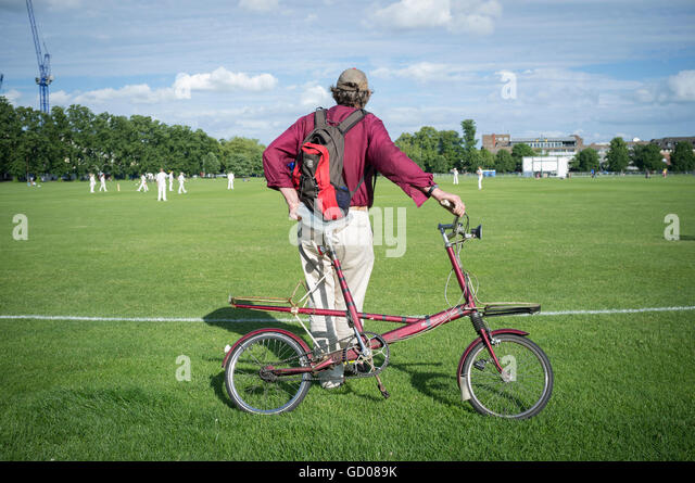 Man leans against his bike whilst watching cricket - Stock Image