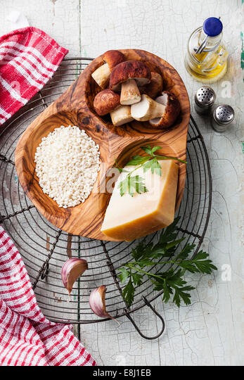 Raw white rice in olive wood bowl with ingredients for risotto with wild mushrooms - Stock Image