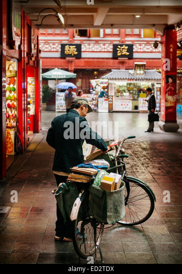 Postman delivering mail by bike in the Old city of Shanghai, China 2014 - Stock Image