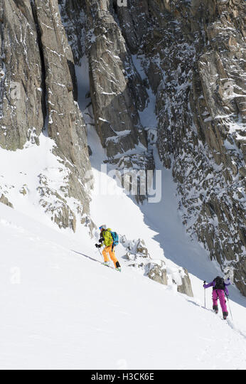 Two woman freerider on a steep ascent along cliffs - Stock Image