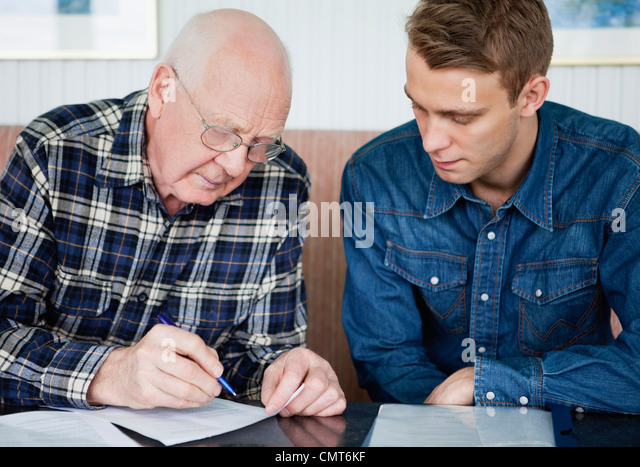 Young man helping grandfather to fill in a form - Stock Image
