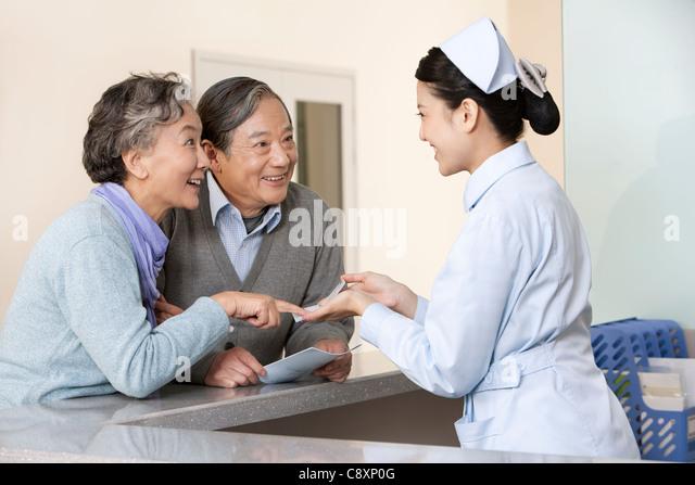 Young Nurse Helping Senior Couple at Nurses' Station - Stock Image