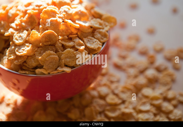Breakfast cereal flakes spilling overflowing bowl - Stock Image